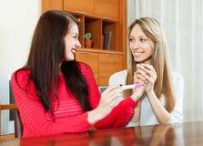 Glückliche Mädchen, die Schwangerschaftstest betrachten Lizenzfreie Stockbilder