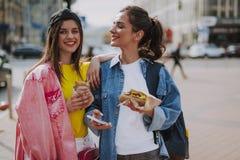 Glückliche Mädchen, die um Stadt mit Würstchen gehen lizenzfreie stockfotografie