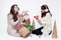 Glückliche Mädchen, die Weihnachtsgeschenke auf weißem Hintergrund öffnen Stockfotografie