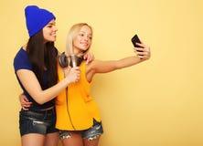 Glückliche Mädchen mit Smartphone über gelbem Hintergrund Glücklicher Selbst Lizenzfreie Stockfotografie