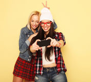 Glückliche Mädchen mit Smartphone über gelbem Hintergrund Glücklicher Selbst Lizenzfreie Stockfotos