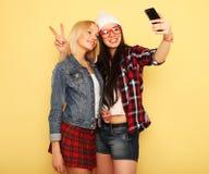 Glückliche Mädchen mit Smartphone über gelbem Hintergrund Glücklicher Selbst Stockbilder