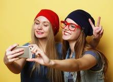 Glückliche Mädchen mit Smartphone über gelbem Hintergrund Glücklicher Selbst Lizenzfreie Stockbilder