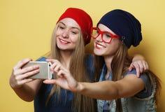 Glückliche Mädchen mit Smartphone über gelbem Hintergrund Glücklicher Selbst Stockfotos