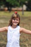 Glückliche Mädchenbalance mit Apfel auf ihrem Kopf Lizenzfreies Stockbild