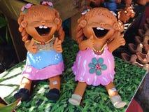 Glückliche Mädchenbodenpuppe dekorativ im Garten lizenzfreie stockfotos