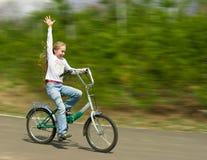 Glückliche Mädchenfahrräder Stockfoto
