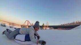 Glückliche Mädchenfahrten und lächelndes snowtube auf schneebedeckte Straßen Langsame Bewegung Schneewinterlandschaft Draußen Spo stock video