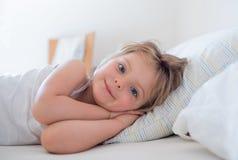 Glückliche Mädchentochter, die das Lächeln aufwacht, Kamera auf Elternteil ` s Bett betrachtend am Morgen Glückliches entspanntes Lizenzfreies Stockfoto