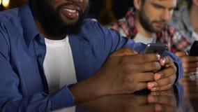 Glückliche Männer in der Kneipe Frauenprofile durch die Datierung von Website auf Smartphone überprüfend stock video