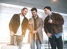Glückliche Männer, die am Telefon am Flughafen aufpassen stockbild