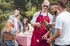 Glückliche Männer, die während des Gartenfests mit Freunden zujubeln stockfoto