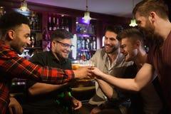 Glückliche männliche Freunde, die Bier trinken und Gläser an der Bar klirren Stockfotografie