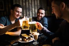 Glückliche männliche Freunde, die Bier trinken und Gläser an der Bar oder an der Kneipe klirren Lizenzfreie Stockfotos