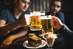 Glückliche männliche Freunde, die Bier trinken und Gläser an der Bar oder an der Kneipe klirren Stockfoto