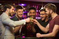 Glückliche männliche Freunde, die Bier trinken und Gläser klirren Lizenzfreies Stockbild