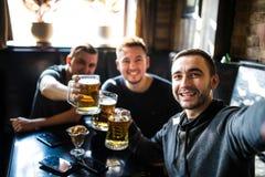 Glückliche männliche Freunde, die Bier trinken und selfie mit Smartphone an der Bar oder an der Kneipe nehmen Lizenzfreie Stockfotografie