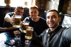 Glückliche männliche Freunde, die Bier trinken und selfie mit Smartphone an der Bar oder an der Kneipe nehmen lizenzfreie stockfotos