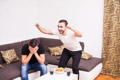 Glückliche männliche Freunde, die zu Hause Fußballteam stützen Ein Mann glücklich, anderer traurig Stockbild