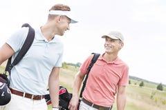 Glückliche männliche Golfspieler, die gegen klaren Himmel sich unterhalten Stockbild