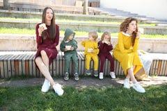 Glückliche Mütter mit Kindern in der modernen Sportkleidung im Familienstil stockfotografie