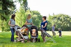 Glückliche Mütter mit Kinderwagen Stockbild