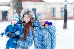 Glückliche Mütter und babys, die auf Schnee spielen stockfotografie