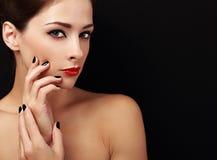 Glückliche Make-upfrau, die mit den roten Lippen und den schwarzen Fingern auf Schwarzem schaut Lizenzfreies Stockfoto