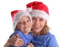 Glückliche Mama mit dem Sohn in den Weihnachtsschutzkappen lizenzfreie stockfotografie