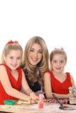 Glückliche Mamma mit den Doppeltöchtern, die Plätzchen verzieren Lizenzfreie Stockfotos