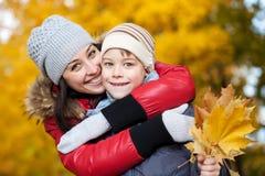 Glückliche Mamma und Sohn spielen in einem gelben Herbst Stockfotos