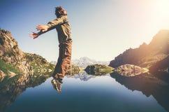 Glückliche Mann-Fliegenlevitation, die mit See und Bergen auf Hintergrund springt stockfotos