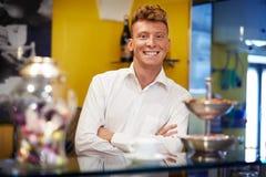 Glückliche Mannfunktion als Kellner, der in der Stange lächelt Stockfotografie