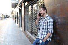 Gl?ckliche Manngespr?che am Telefon, das auf einer Wand in der Stra?e sich lehnt lizenzfreie stockfotografie