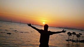 Glückliche Mannwege auf dem Strand zum Meer bei erstaunlichem Sonnenuntergang hebt Hände in der Zeitlupe an 1920x1080 stock video