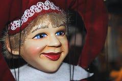 Glückliche Marionette - lächelnde Spassvogel mit einer roten Kappe und blauen Augen Lizenzfreie Stockfotos