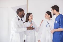 Glückliche medizinische Berater, die in der hellen Klinik sprechen Lizenzfreie Stockbilder