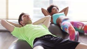 Glückliche Menschen, die Bauchmuskeln auf fitball biegen stock footage
