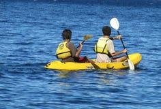 Glückliche Menschen, die in den Kajaks tragen Schwimmwesten mit Paddel schwimmen Lizenzfreie Stockfotografie