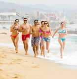 Glückliche Menschen, die am Strand laufen Stockfotografie