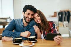 Glückliche Menschen, die Telefon im Café, Fotos machend verwenden stockbilder