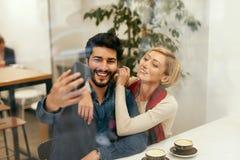 Glückliche Menschen, die Telefon im Café, Fotos machend verwenden stockbild