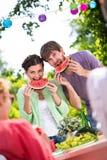 Glückliche Menschen, die Wassermelone essen lizenzfreies stockfoto