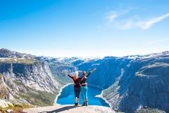 Glückliche Menschen entspannen sich in der Klippe während der Reise Norwegen Trolltunga, das Weg wandert stockbilder