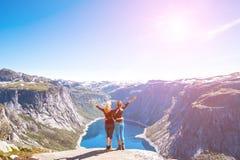 Glückliche Menschen entspannen sich in der Klippe während der Reise Norwegen Trolltunga, das Weg wandert Tonen des Bildes Lizenzfreies Stockbild