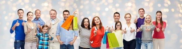 Glückliche Menschen mit den Einkaufstaschen, die sich Daumen zeigen lizenzfreies stockfoto