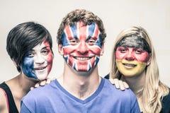 Glückliche Menschen mit europäischen Flaggen auf Gesichtern Stockbilder