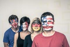 Glückliche Menschen mit Flaggen auf Gesichtern Stockfotos
