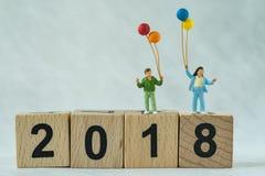 Glückliche Miniaturfamilie, welche die Ballone stehen auf Holzklotz hält Stockbilder