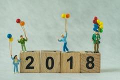 Glückliche Miniaturfamilie, welche die Ballone stehen auf Holzklotz hält Lizenzfreies Stockfoto